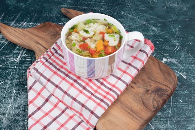 Овощной суп на деревянной доске со скатертью. фото высокого качества