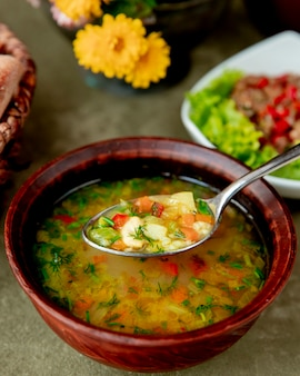 Vegetable soup served with herbs