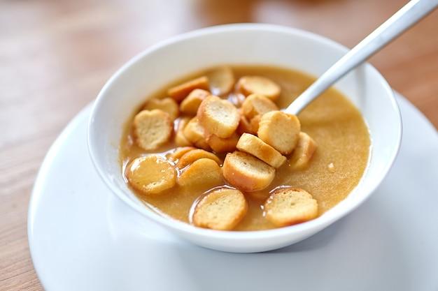 木製のテーブルの上に立っている白いボウルにパン粉と野菜スープ