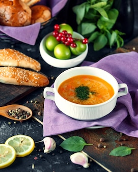 Vegetable soup with chopped herbs and bakery