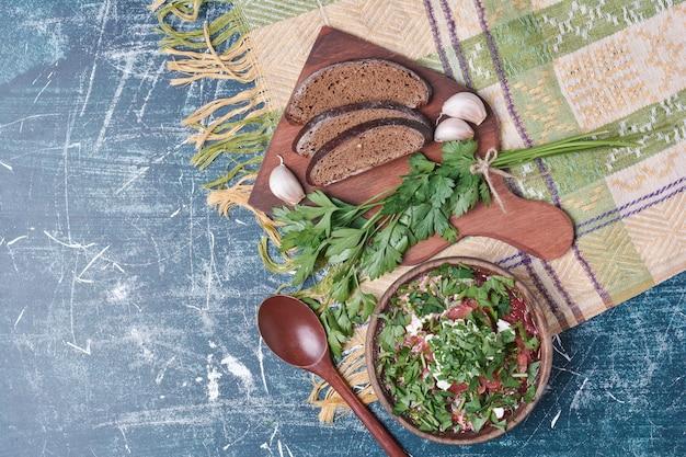 허브와 향신료를 곁들인 야채 수프는 어두운 빵과 함께 제공됩니다.
