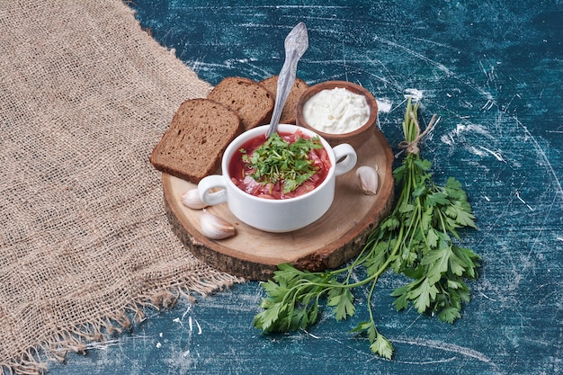 Zuppa di verdure con erbe e spezie servita con yogurt e pane nero.
