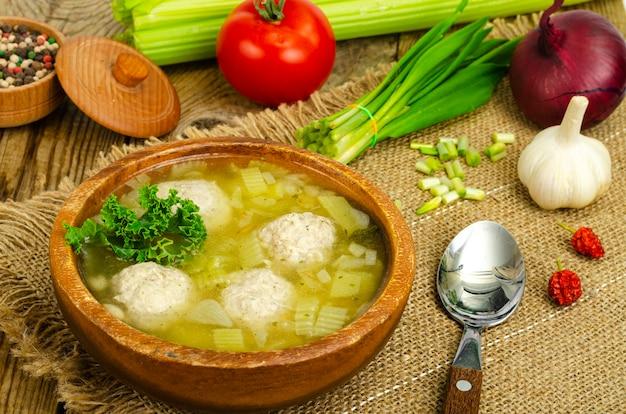 Овощной суп с фрикадельками, овощами на фоне. студийное фото