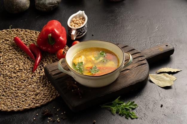Овощной суп с лососем, картофелем и сладким перцем, украшенный лавровым листом петрушки и помидорами черри.