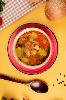 Vegetable soup with sesame bun and wooden spoon