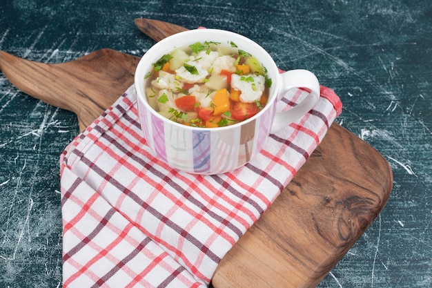 Vegetable soup on wooden board with tablecloth. high quality photo