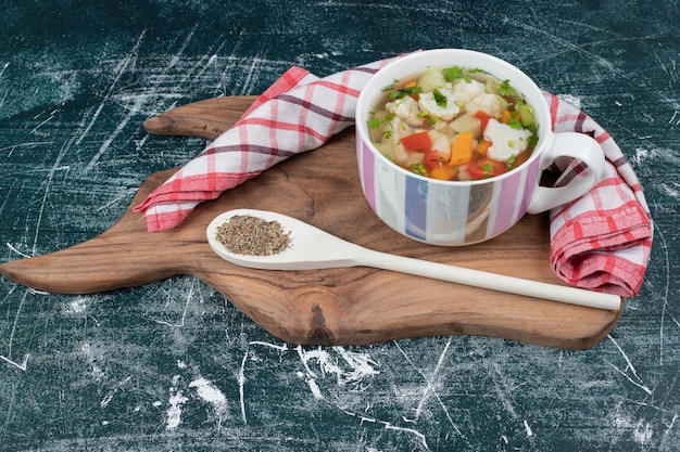 Vegetable soup on wooden board with tablecloth and spoon. high quality photo