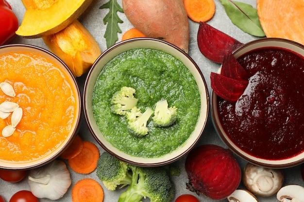 Овощные супы и ингредиенты на сером, вид сверху