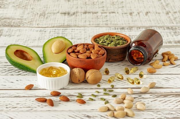 オメガ3酸の野菜源。バランスの取れた食事の概念。アボカド、ナッツ、木製の背景に油、