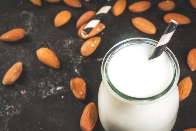 Растительные источники белка. веганская здоровая пища. маленькая бутылка порции миндального молока. на фоне орехов миндаль на черном бетонном столе. выборочный фокус.