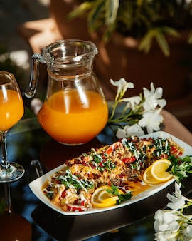 Vegetable stew garnished with herbs and lemon, served with orange juice