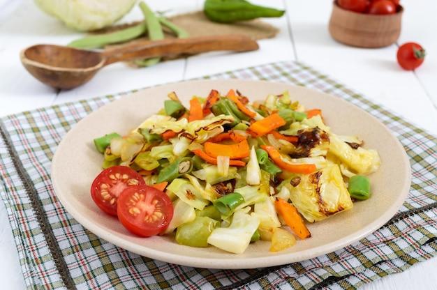 Овощное рагу на тарелке на белом деревянном столе