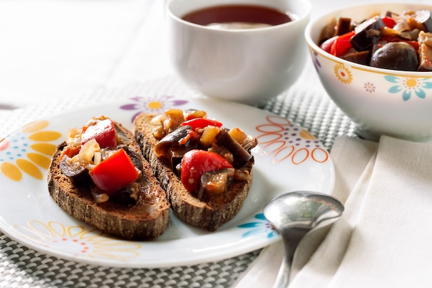 Vegetable stew with eggplant, red pepper and tomatoes on toasted rye bread