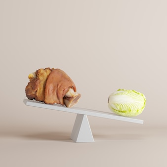 Vegetable tipping seesaw with pork leg on opposite end on pastel background. food idea minimal.