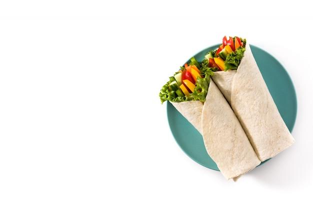 白い表面上に分離された野菜のトルティーヤラップトップビューコピースペース