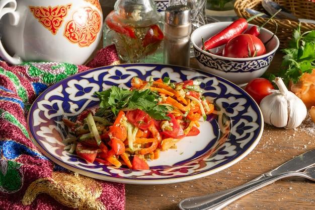 Овощной веганский салат хоровац из запеченных баклажанов, помидоров, моркови и болгарского перца в тарелке с традиционным узбекским узором