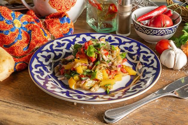 伝統的なウズベックパターンのプレートにトマト、きゅうり、大根、ピーマン、赤玉ねぎ、レタスの葉の野菜ビーガンサラダ