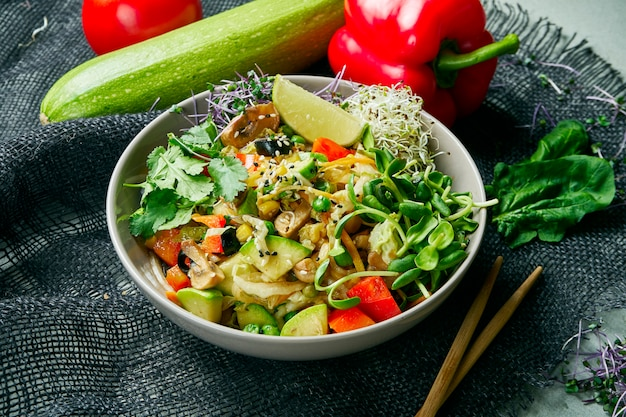 Vegetable vegan wok in a gray bowl on a gray cloth in a composition with vegetables. delicious vegetarian food. diet menu.
