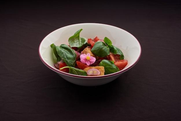 Овощной вегетарианский салат с помидорами, перцем и луком на кухонном столе