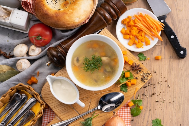 Овощной вегетарианский суп с грибами, морковью и укропом в тарелке с традиционным узбекским
