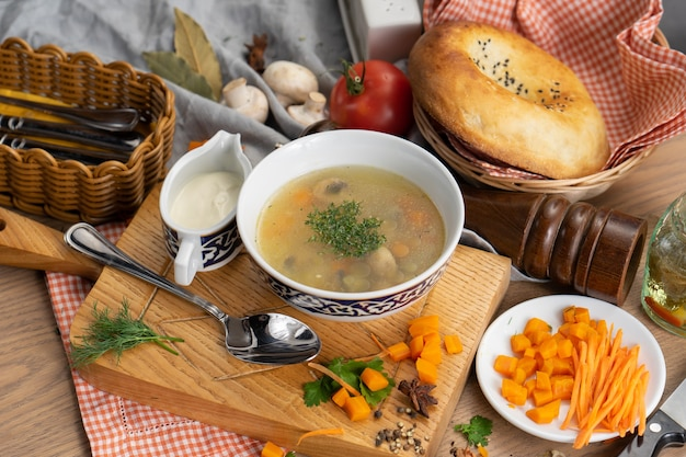 Vegetable vegetarian soup with mushrooms carrots and dill in a plate with a traditional uzbek