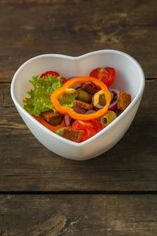 나무 테이블에 접시에 야채 비타민 샐러드. 세로 사진