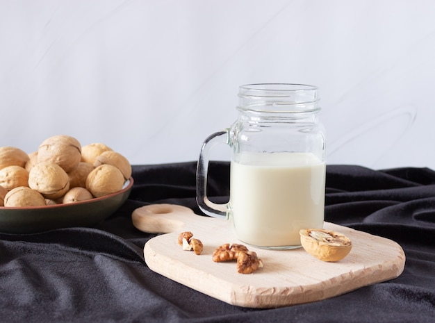 Vegetable walnut milk in a glass cup with a handle on a wooden cutting board