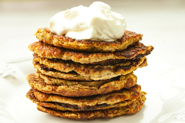 Vegetable zucchini fritters stack served sour cream on on white plate close up. healthy vegetarian vegetable fritters. selective soft focus.