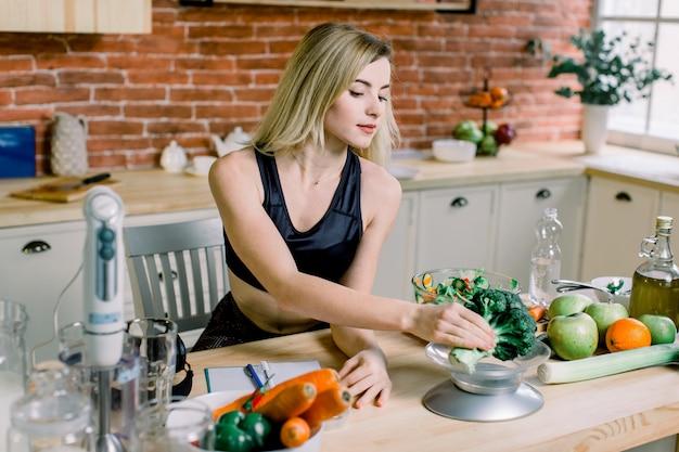 Молодая женщина варя vegetable салат и брокколи весов пока сидящ в кухне на предпосылке красной кирпичной стены. концепция диеты. здоровая пища и образ жизни. готовим дома.