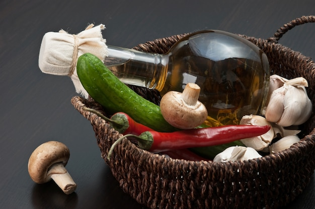 Овощи и корзина с бутылкой уксуса