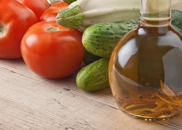 野菜と油のボトル、木製のテーブルのある静物