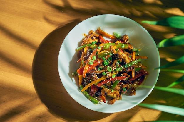 野菜と牛肉の甘酸っぱいソースにシチャンペッパーを添えて。木の背景。中華料理