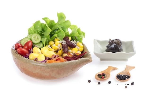 Салат из овощей и хлопьев в миске на белом фоне.