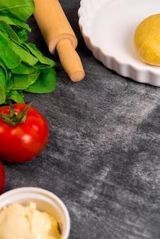 灰色の木製の表面上の野菜と生地