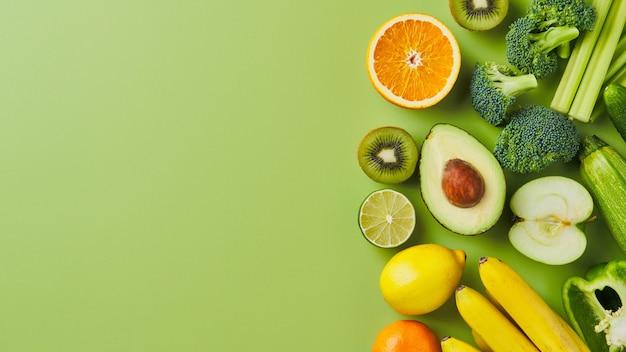 緑の背景に野菜や果物のフレーム水平フラットレイコピースペース