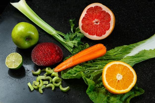 Овощи и фрукты здоровой пищи выпадают на темный стол. свежий апельсин, яблоко, лайм, морковь, салат, свекла и сельдерей.