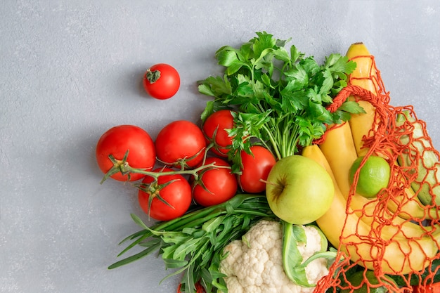 Овощи и фрукты в эко-сумке на сером фоне, вид сверху.