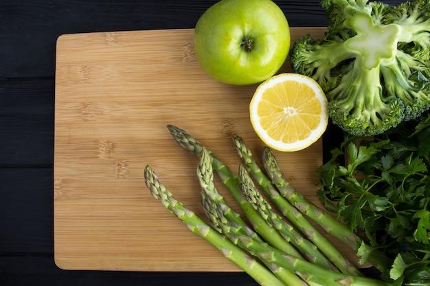 黒い木製の背景に茶色のまな板に野菜や果物。上面図。コピースペース。健康食品。