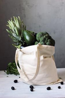 白い木製のテーブルの上のエコバッグに野菜や果物の製品