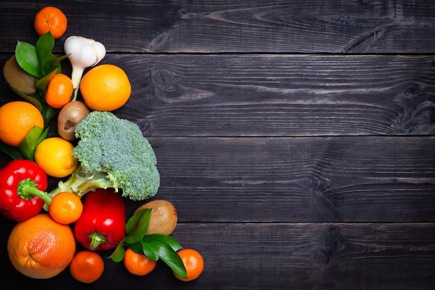 Овощи и фрукты для поддержания иммунитета на черном фоне. копировать пространство