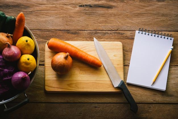 ノートブックとまな板の上の野菜とナイフ