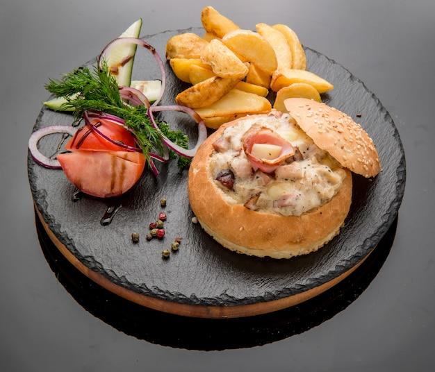 Запеченная булочка с овощами и мясом с ветчиной, сыром и зеленью