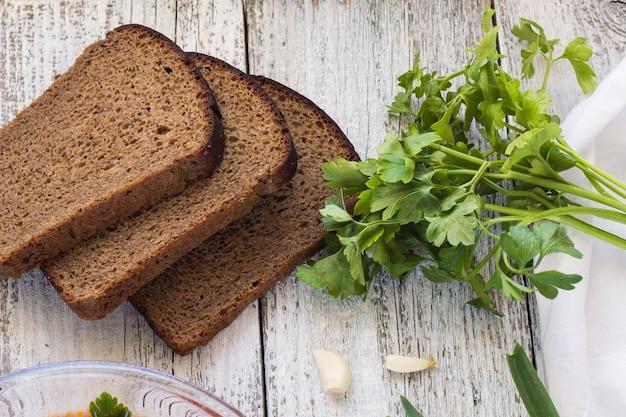 赤いビーツのスープまたはサワークリームとボルシチの野菜と肉。パン、ねぎ、パセリ、にんにくを金属スプーンで皿の周りに