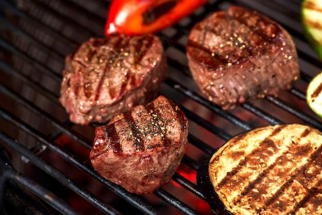 野菜と肉が炎でグリルで焼けるように、クローズアップ