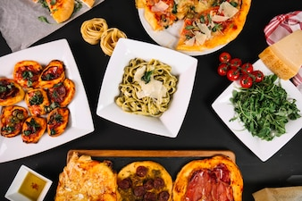 Vegetables and pizzas near pasta