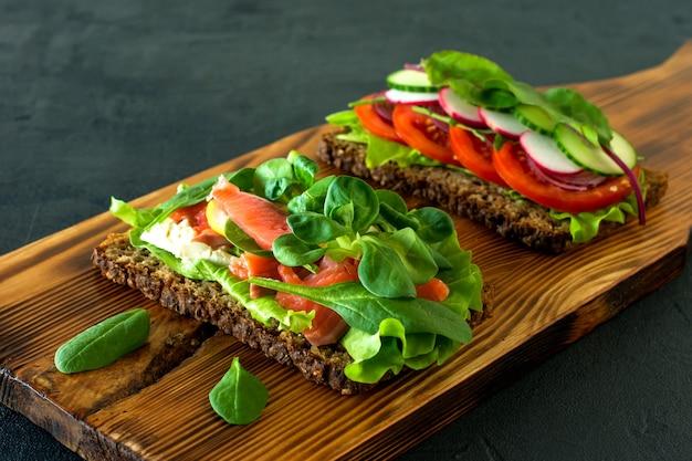 野菜とスモークサーモンのオープンサンドイッチの格子、木製の机の上のトマト。健康的な朝食