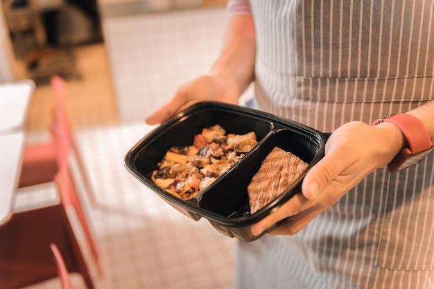 Овощи и стейк. официант в полосатом фартуке держит ланч-бокс с тушеными овощами и мясным стейком