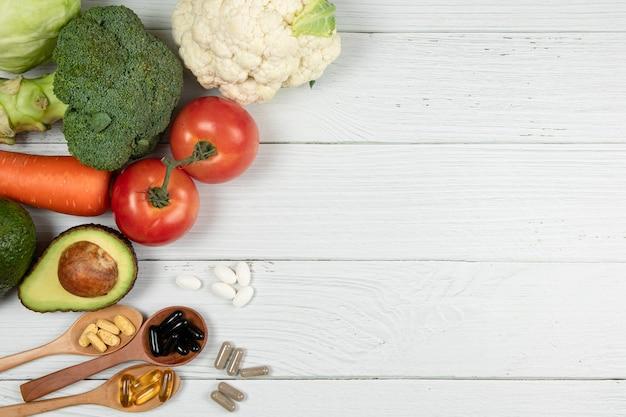 白い木製のテーブルに置かれた野菜とビタミン