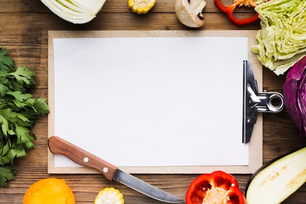 Vegetables assortment on wooden background with empty clipboard