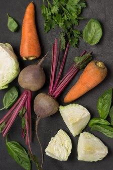 야채. 채소, 씻지 않은 당근, 다진 양배추, 파슬리 및 바질이 들어간 비트. 검정색 배경. 플랫 레이